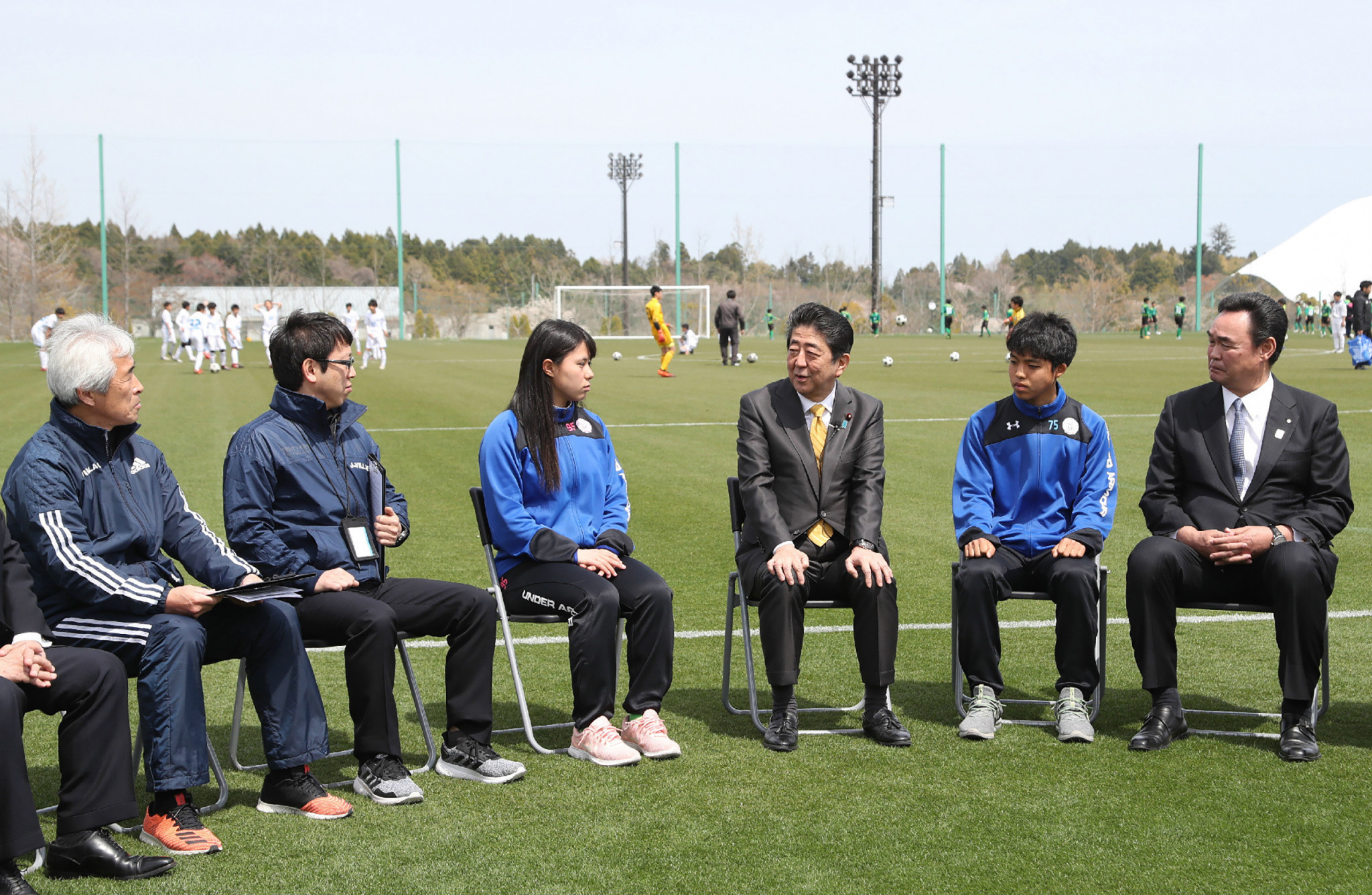 Japanese Prime Minister Shinzo Abe, third right, speaks to local schoolchildren at the re-opened J-Village ©Getty Images
