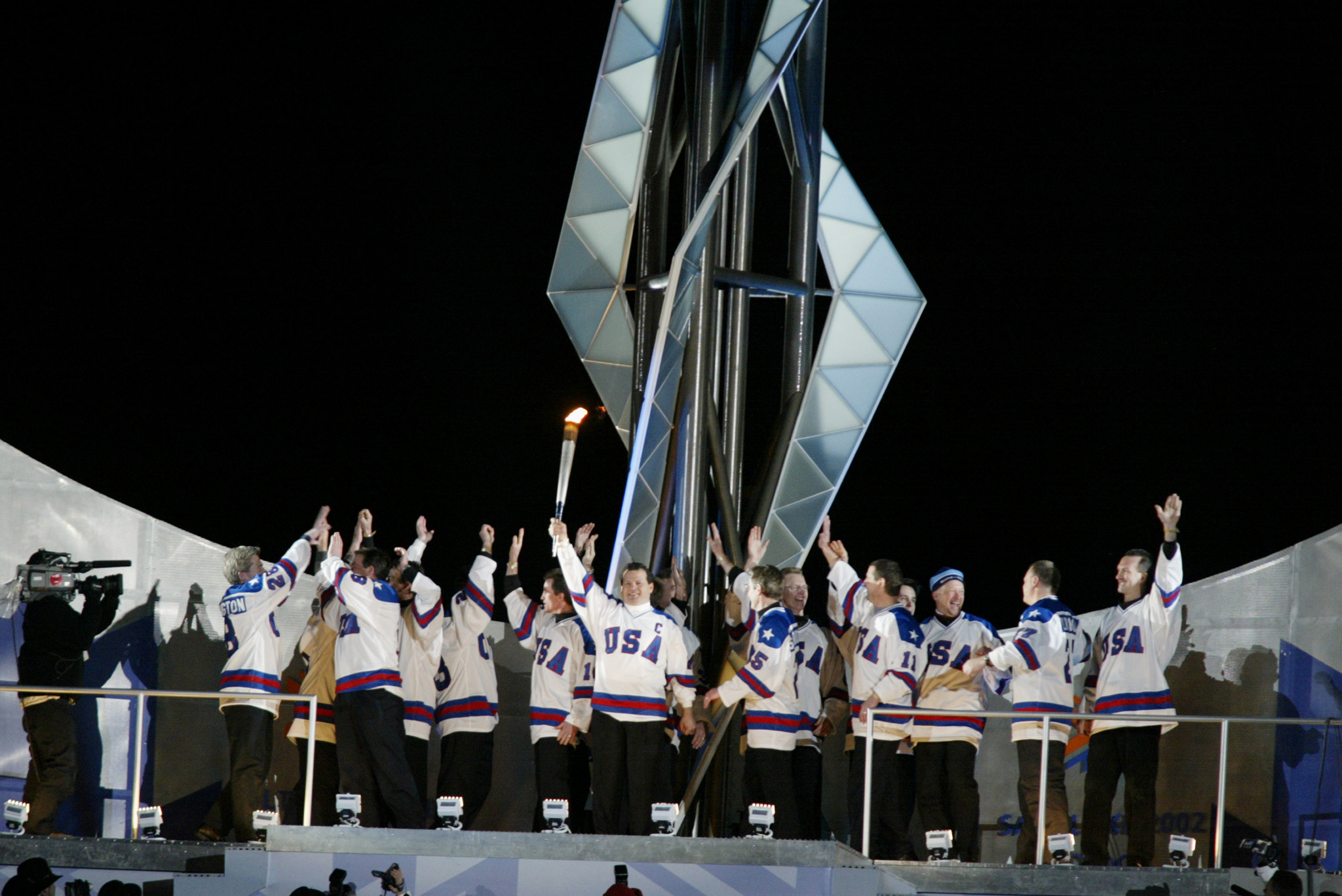 The US team which won the ice hockey title at the Lake Placid 1980 Olympics lights the Cauldron at the Opening Ceremony of the Salt Lake City 2002 Winter Games ©Getty Images