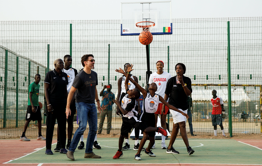 Canadian Prime Minister Justin Trudeau tossing the ball up between two young Senegalese athletes from under the watchful eye of Kayla Alexander, who qualified as one of the players to represent Canada at Tokyo 2020 ©COC