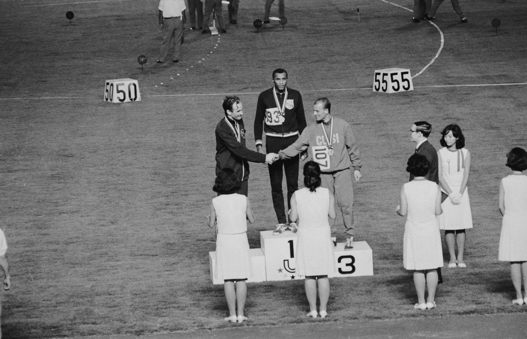 The three winners of the men's 200 metres dash mount the rostrum at the World University Games in Tokyo, held at the Universiade, 7th September 1967. From left to right, they are Britain's Menzies Cambell, T. Smith of the USA, and Italy's I. Giani. © Keystone/Hulton Archive/Getty Images