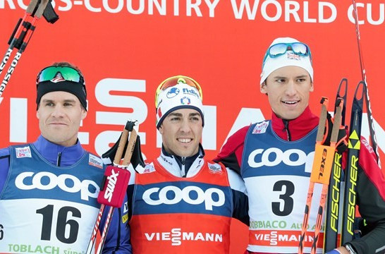 Federico Pellegrino (centre) celebrates his FIS Cross Country World Cup victory in Toblach today ©FIS/Nordic Focus