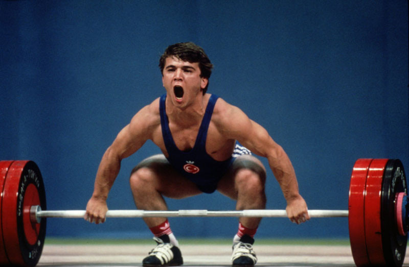 Naim Suleymanogu of Turkey crouches in preparation before lifting a 60kg weight and setting a new world record in the 1988 Seoul Olympic games, South Korea. © Pascal Rondeau/ALLSPORT.