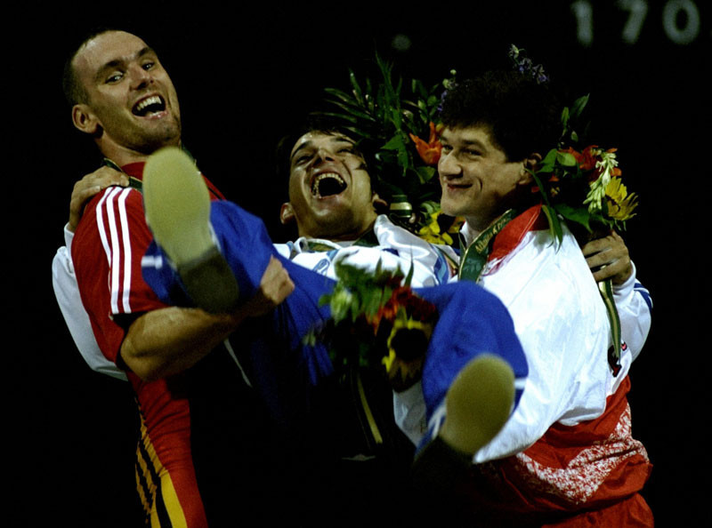 Weightlifting gold medallist Pyrros Dimas of Greece is lifted by M. Huster of Germany, silver, left, and A. Cofalik of Poland, bronze at the Georgia World Congress Centre at the 1996 Centennial Olympic Games in Atlanta, Georgia.