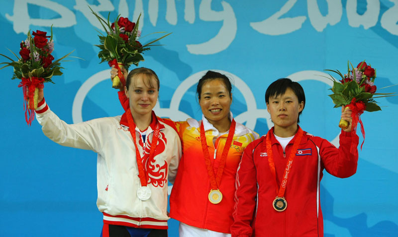 Silver medallist Marina Shainova of Russia, Gold medalist Chen Yanqing of China and Bronze medalist O Jong Ae of North Korea pose on the podium during the medal ceremony for the Women's 58kg group A weightlifting event at the Beijing University of Aeronautics & Astronautics Gymnasium on Day 3 of the Beijing 2008 Olympic Games on August 11, 2008 in Beijing, China. © Stu Forster/Getty Images.