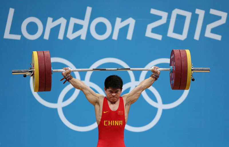 Qingfeng Lin of China competes during the Men's 69kg Weightlifting Final on Day 4 of the London 2012 Olympic Games at ExCeL on July 31, 2012 in London, England. © Quinn Rooney/Getty Images.