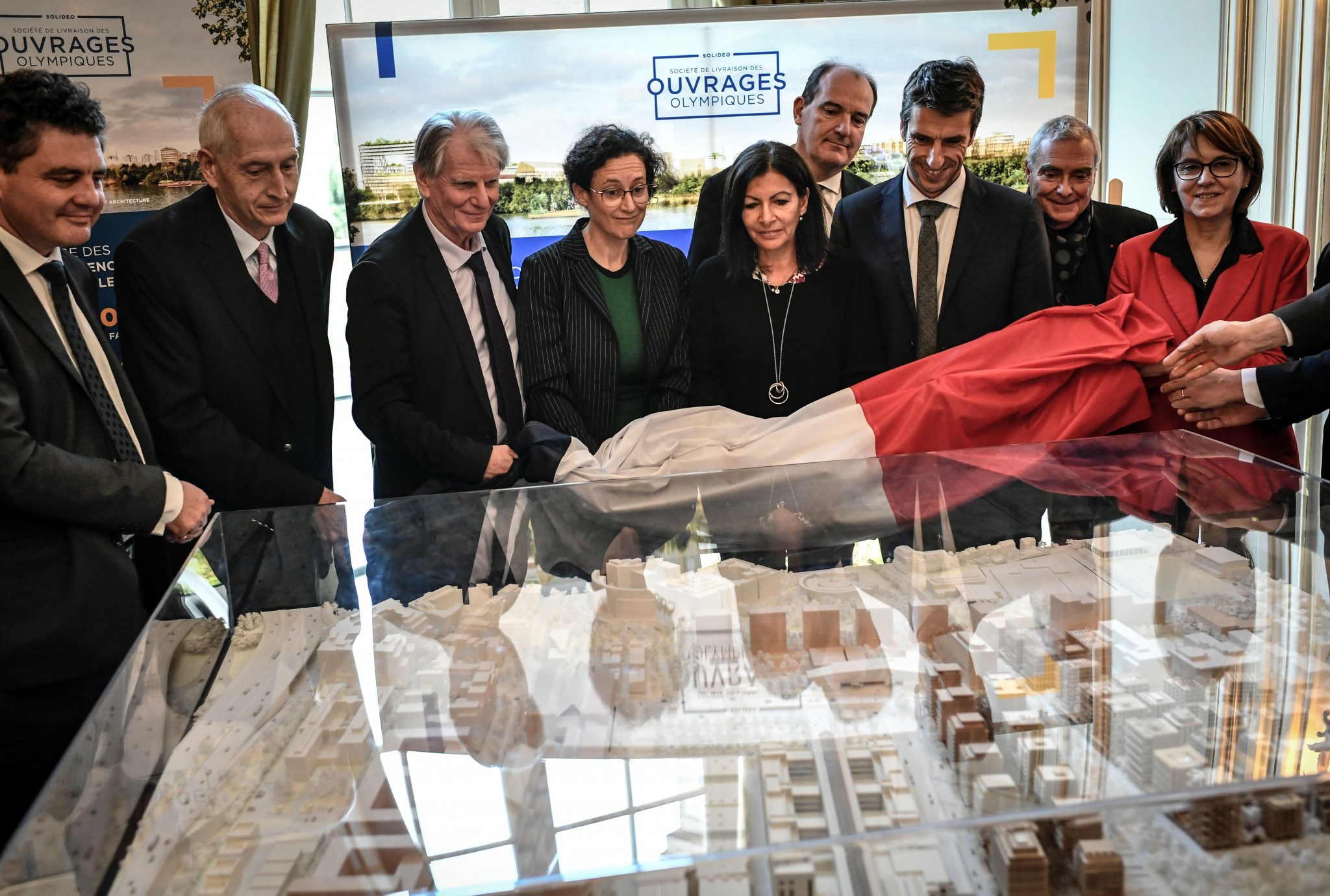 Michel Cadot, second left, looks at a model of the Paris 2024 Olympic Village in a group including Paris Mayor Anne Hidalgo, centre, Jean Castex, fourth from right, and Paris 2024 President Tony Estanguet, third from right ©Getty Images