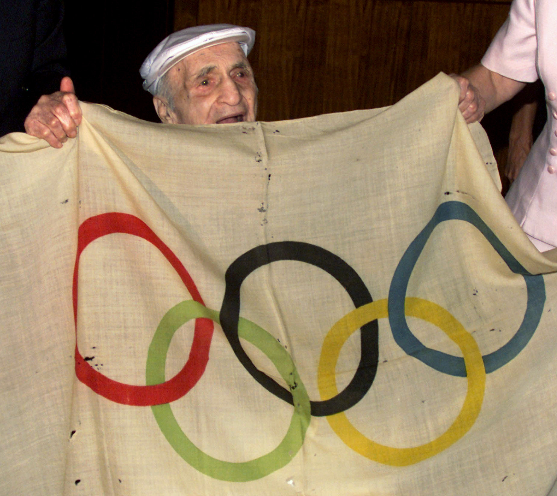 Hal Prieste, then 103, holds the original Olympic flag that he stole from a pole during the 1920 Olympics in Antwerp, where he won a bronze medal in diving. He handed it back to IOC President Juan Antonio Samaranch during the IOC Session in Sydney in 2000 ©Getty Images