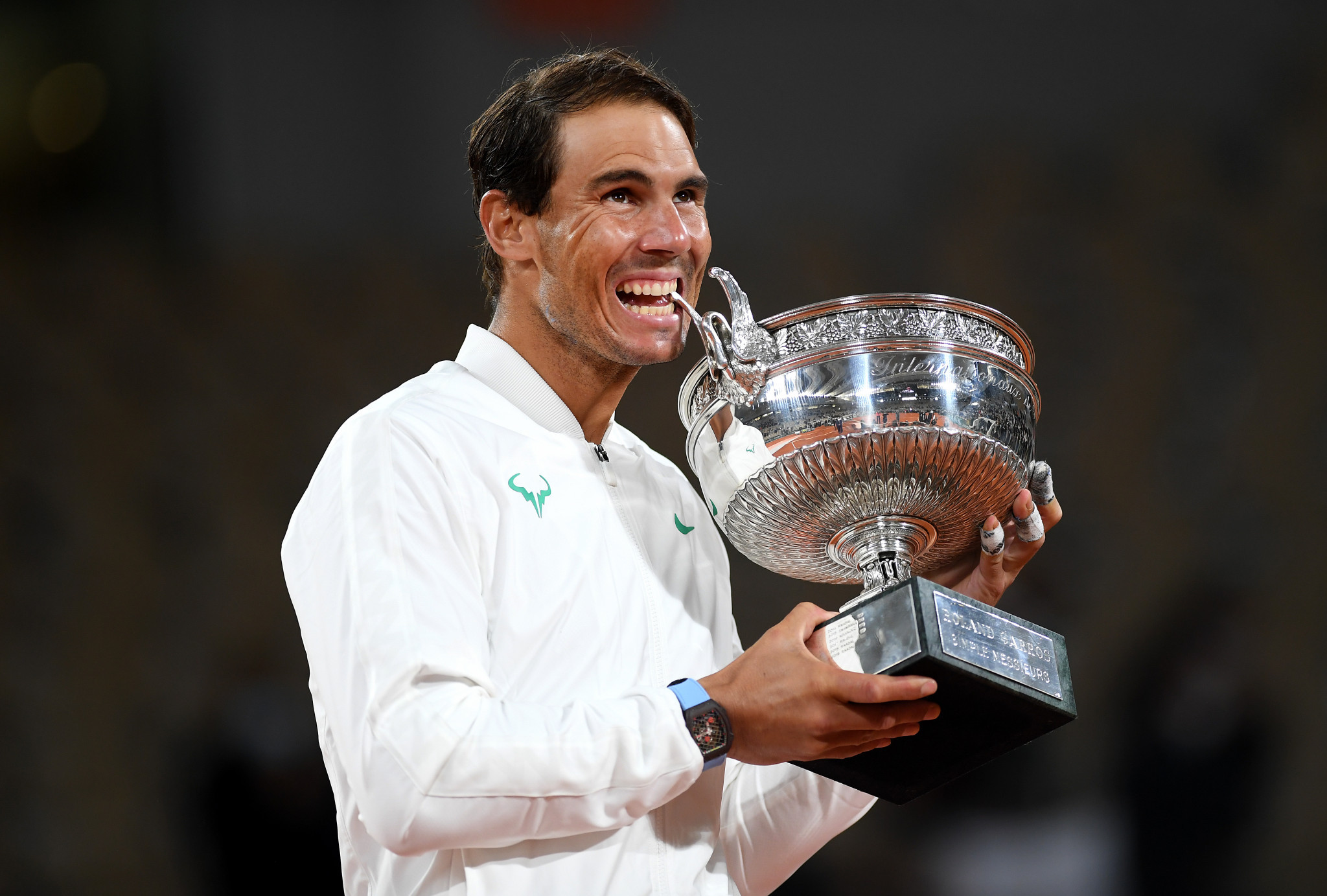 Rafael Nadal bites La Coupe des Mousquetaires after beating Novak Djokovic in straight sets ©Getty Images