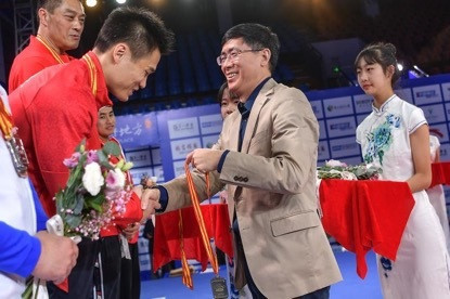 Zhou Jinqiang, President of the Chinese Weightlifting Association, presents the gold medal to Lu Xiaojun ©CWA