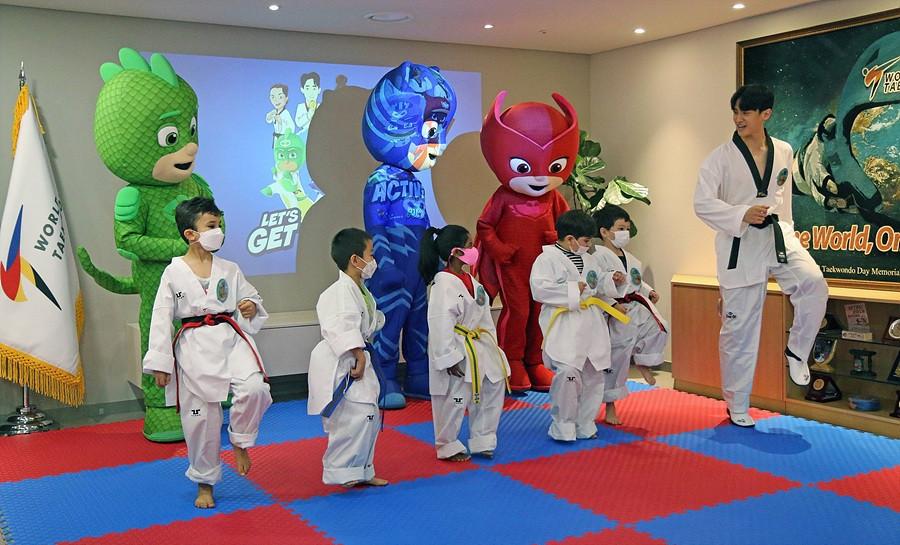 Three-time world champion Lee Dae-hoon teaches children some taekwondo moves ©World Taekwondo