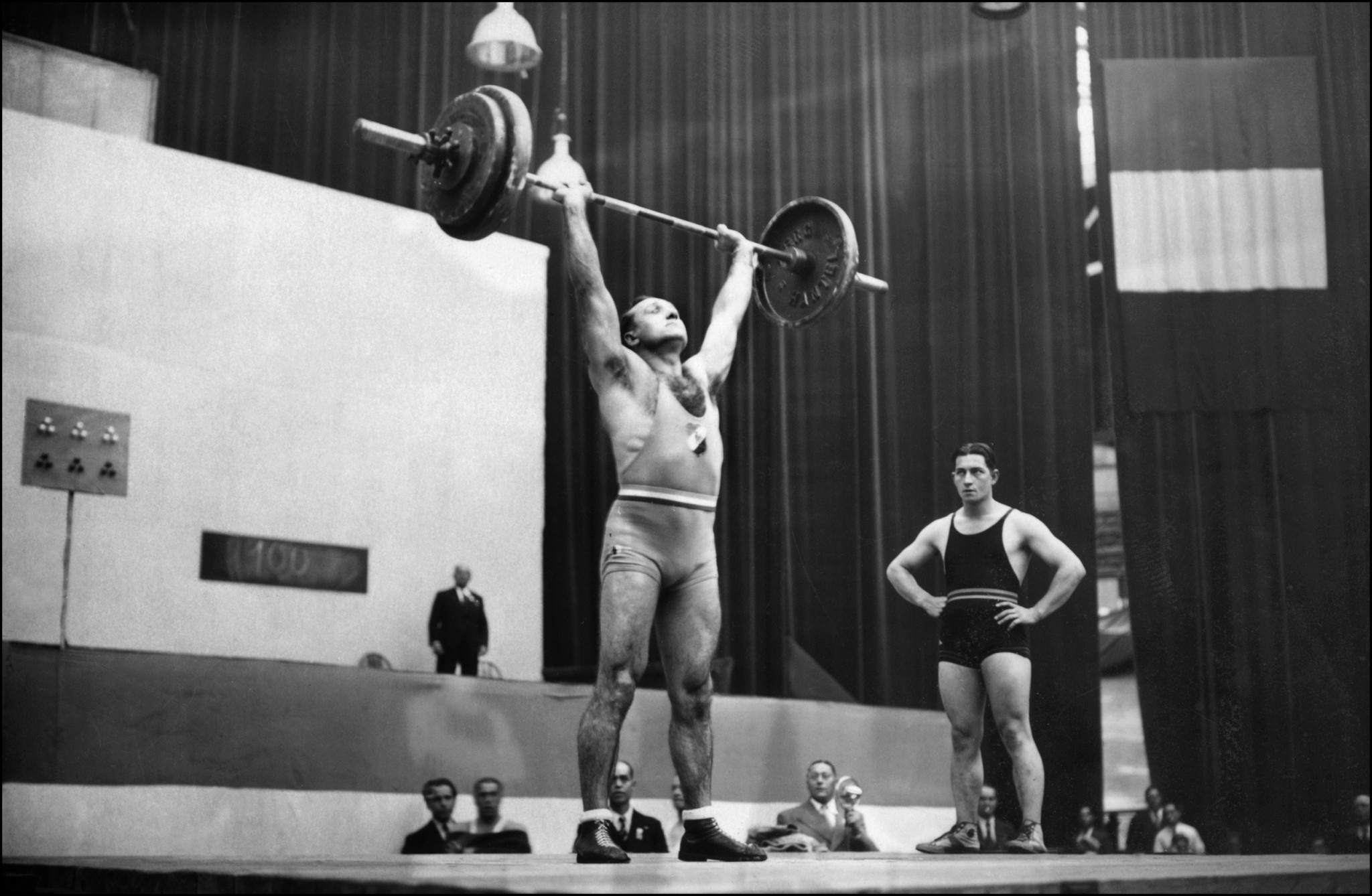 Louis Hostin, best French medal winner in his category, lift weight, 15 September 1937. After taking silver in the Light Heavyweight at the 1928 Olympics in Amsterdam, Hostin won two gold medals at the 1932 los Angeles Olympics and 1936 Berlin Olympics. He was also European champion in 1930 and 1935 and world vice-champion in 1937. Photo credit AFP/AFP via Getty Images.