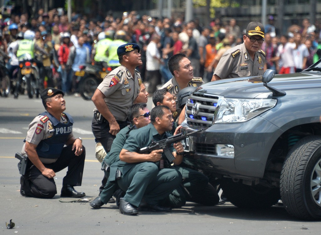 Indonesian police take position behind a vehicle as they pursue suspects after a series of blasts rocked Jakarta ©AFP/Getty Images