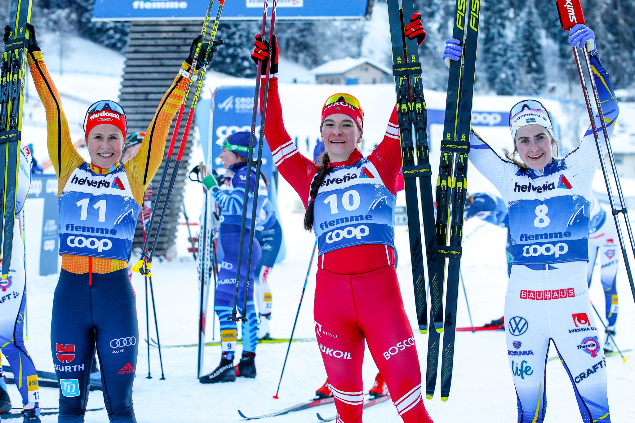 Natalia Nepryaeva, centre, celebrates after winning the 10km classic mass start in Val di Fiemme ©Getty Images