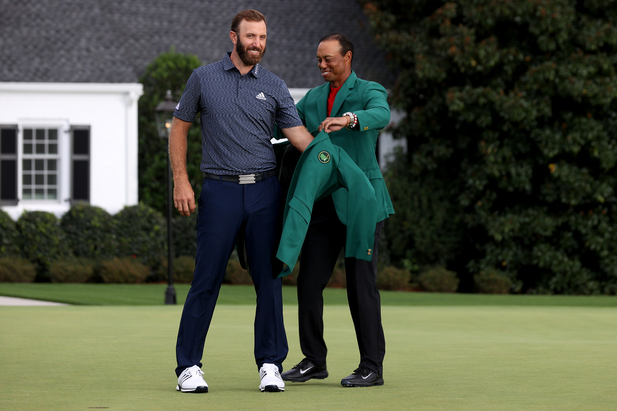 Dustin Johnson receives the green jacket from Tiger Woods after winning The Masters in 2020 ©Getty Images