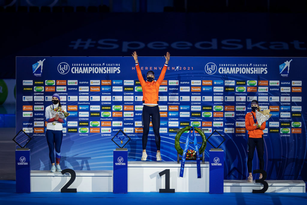 Jutta Leerdam (centre) raises her arms in celebration on the podium after winning the overall European sprint title ©ISU