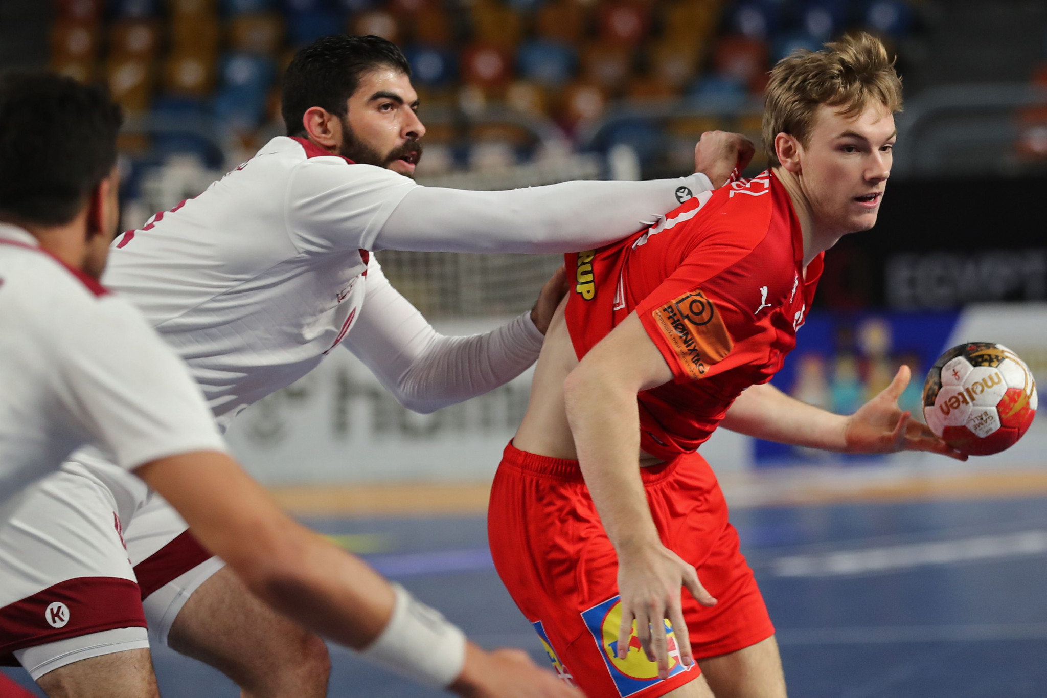 Mathias Gidsel, who scored six goals for Denmark, has his shirt pulled up his back by a Qatari player during their IHF World Men's Handball Championship match ©Getty Images