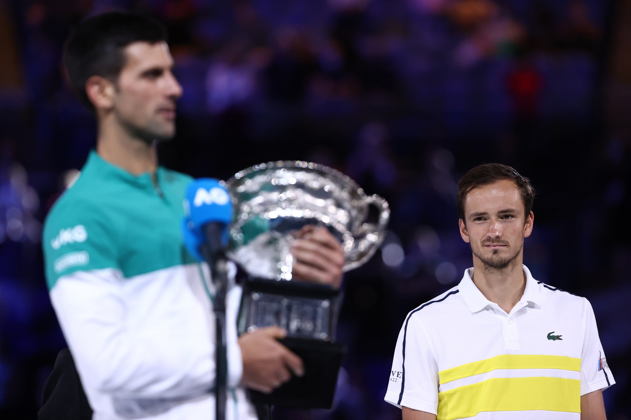 Medvedev watches on as Djokovic gives his victory speech with the trophy in his arms ©Getty Images