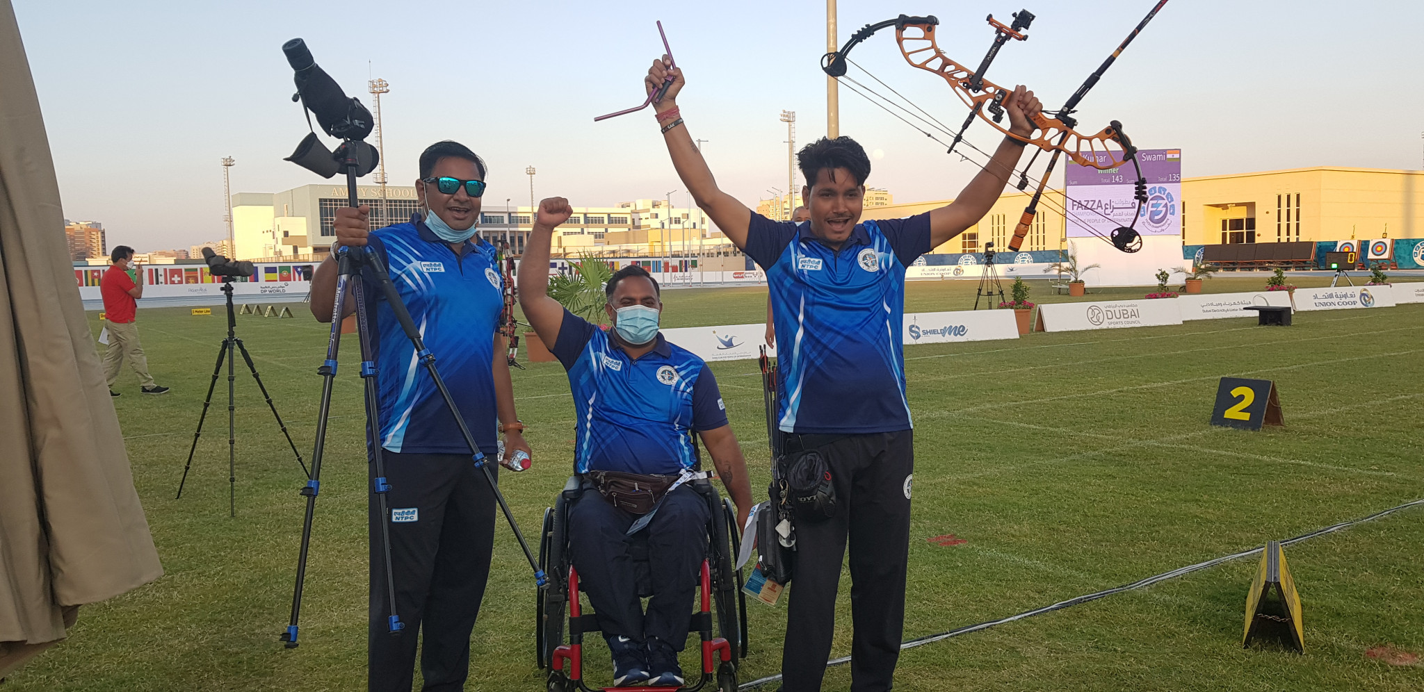 Rakesh Kumar, centre, and Shyam Sundar Swami, right, celebrate their respective gold and silver medals in the men's compound open ©Fazza LOC/PCI