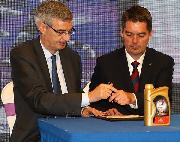 Bertrand de La Noue (left) prepares to add his signature to the host-city certificates during the ceremony in China ©BWF