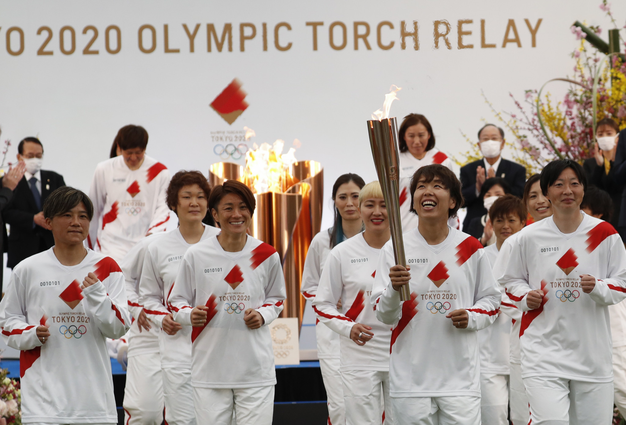 Azusa Iwashimizu was flanked by World Cup-winning team mates as she carried the Olympic Torch ©Getty Images