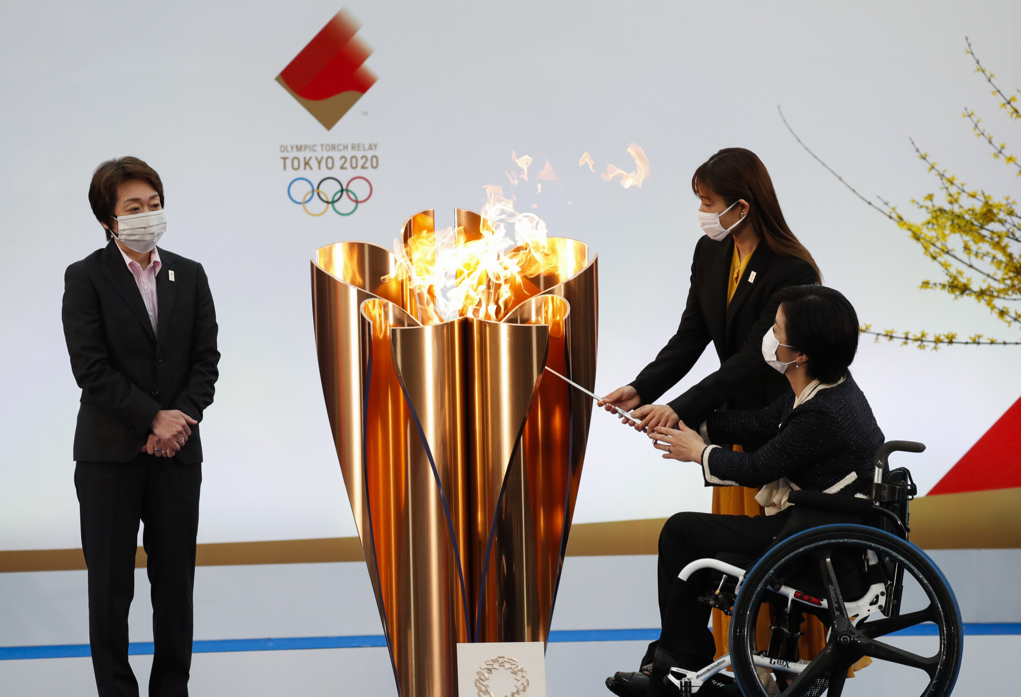 Tokyo 2020 President Seiko Hashimoto, left, watched on as a cauldron was lit by Paralympic shooter Aki Taguchi, right, and actress Satomi Ishihara ©Getty Images