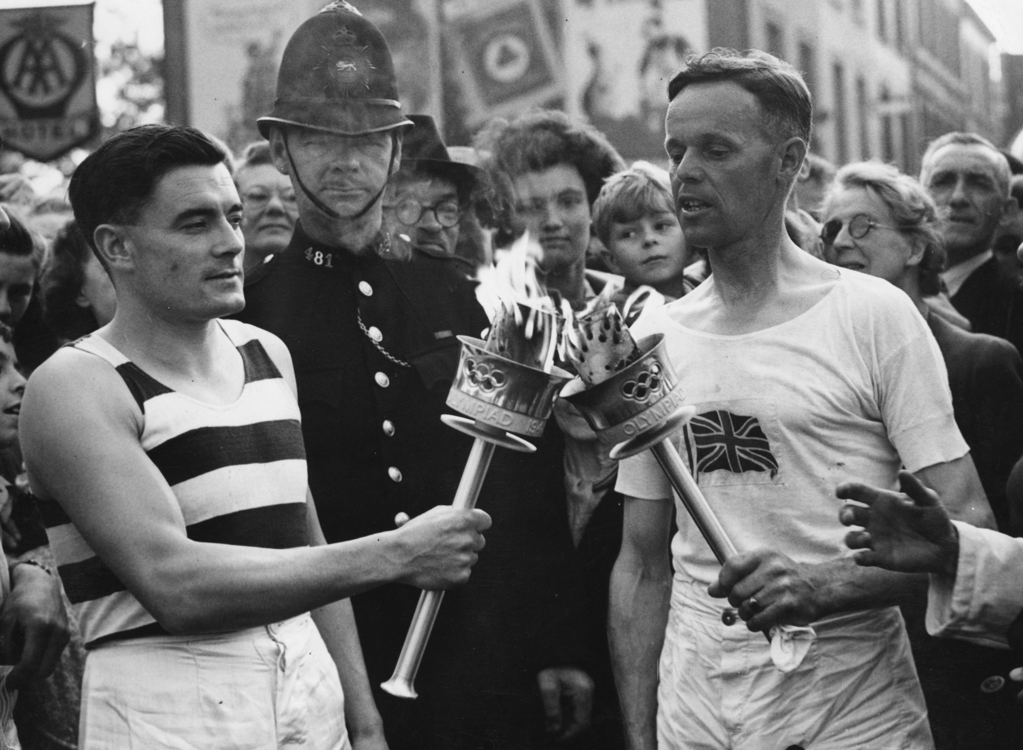 Veteran runner H J Bignall, right, hands the Olympic Torch to Fred Prevett at Redhill during the 1948 Relay from Dover to London ©Getty Images