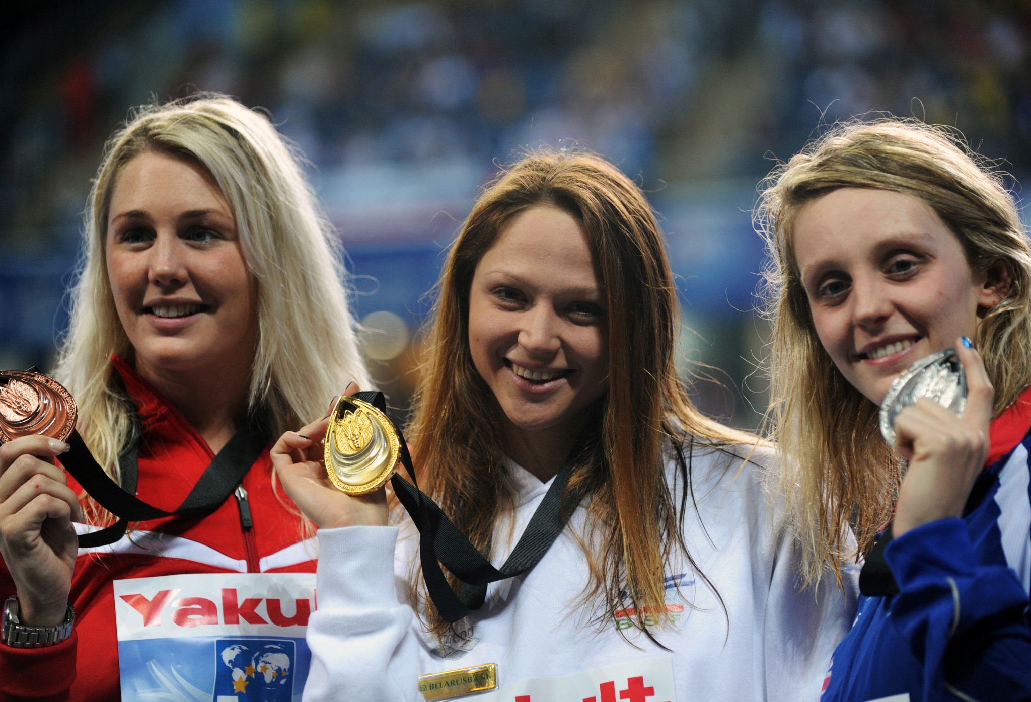 Aliaksandra Heresimenia, centre, with the 2012 World Championships Short Course gold medal that she is now putting up for sale  ©Getty Images