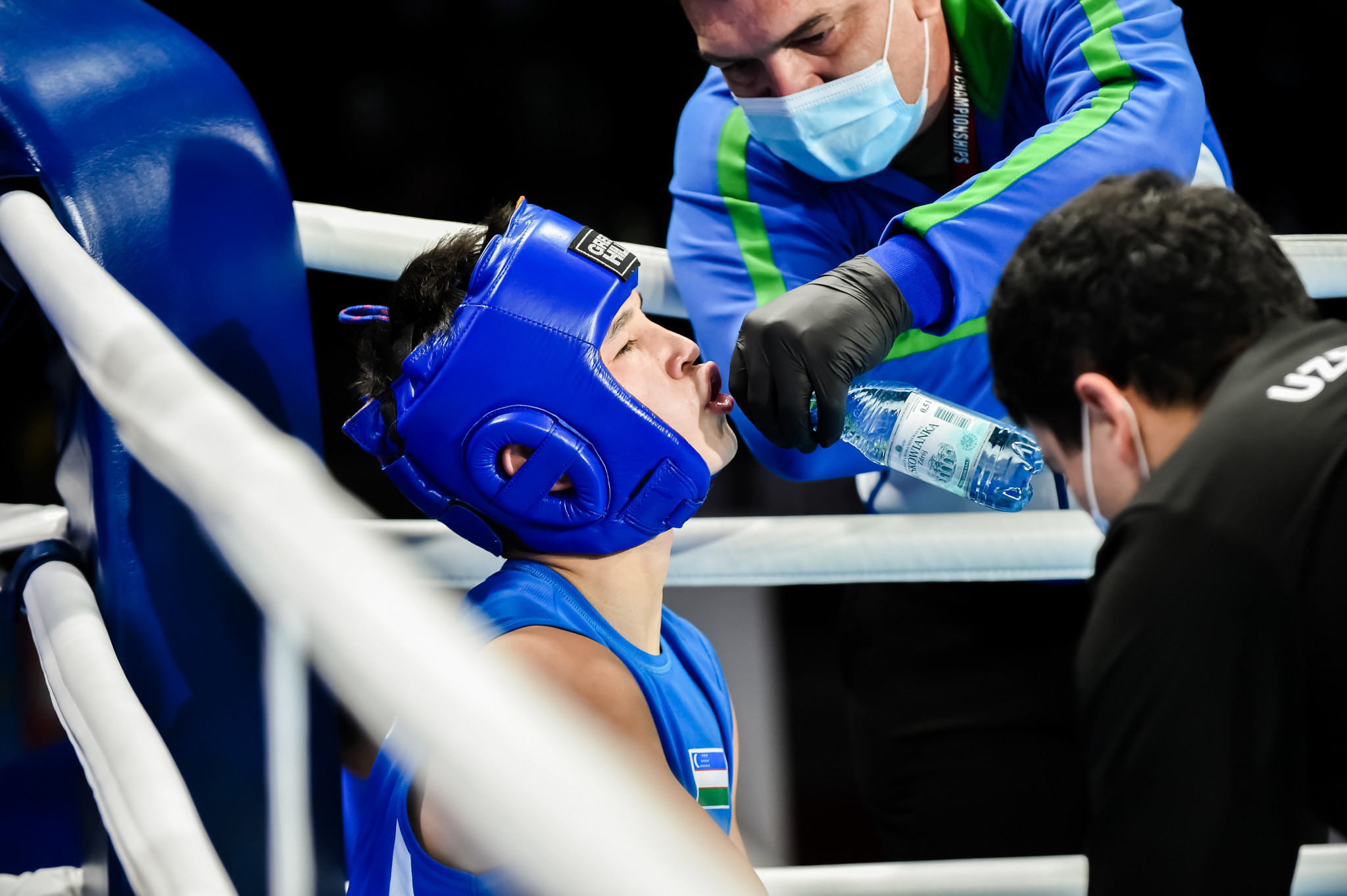 A fighter takes on water during a break between rounds ©AIBA