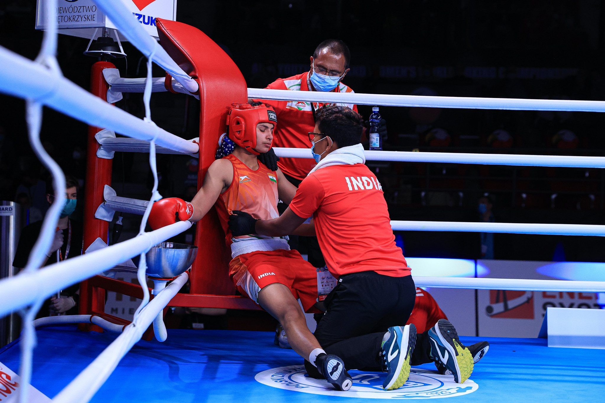 An Indian fighter is attended to by her team during a break between rounds ©AIBA