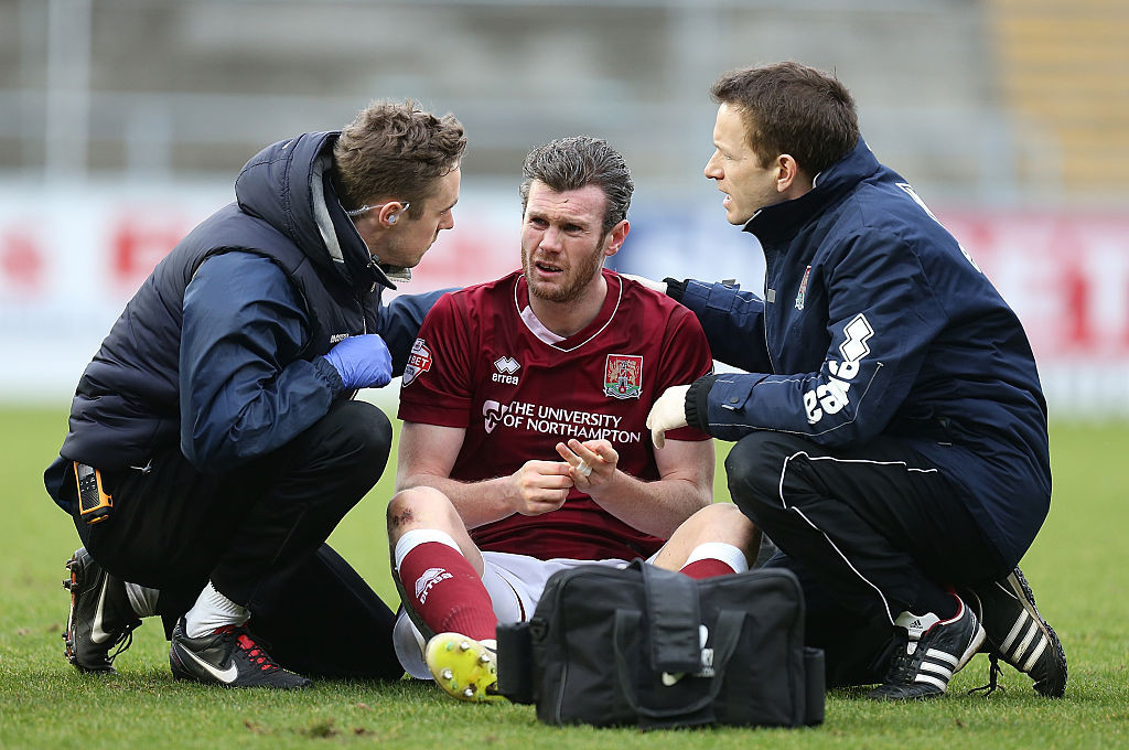 Zander Diamond of Northampton Town receives treatment from physios after a clash of heads left him concussed in a League Two match ©Getty Images