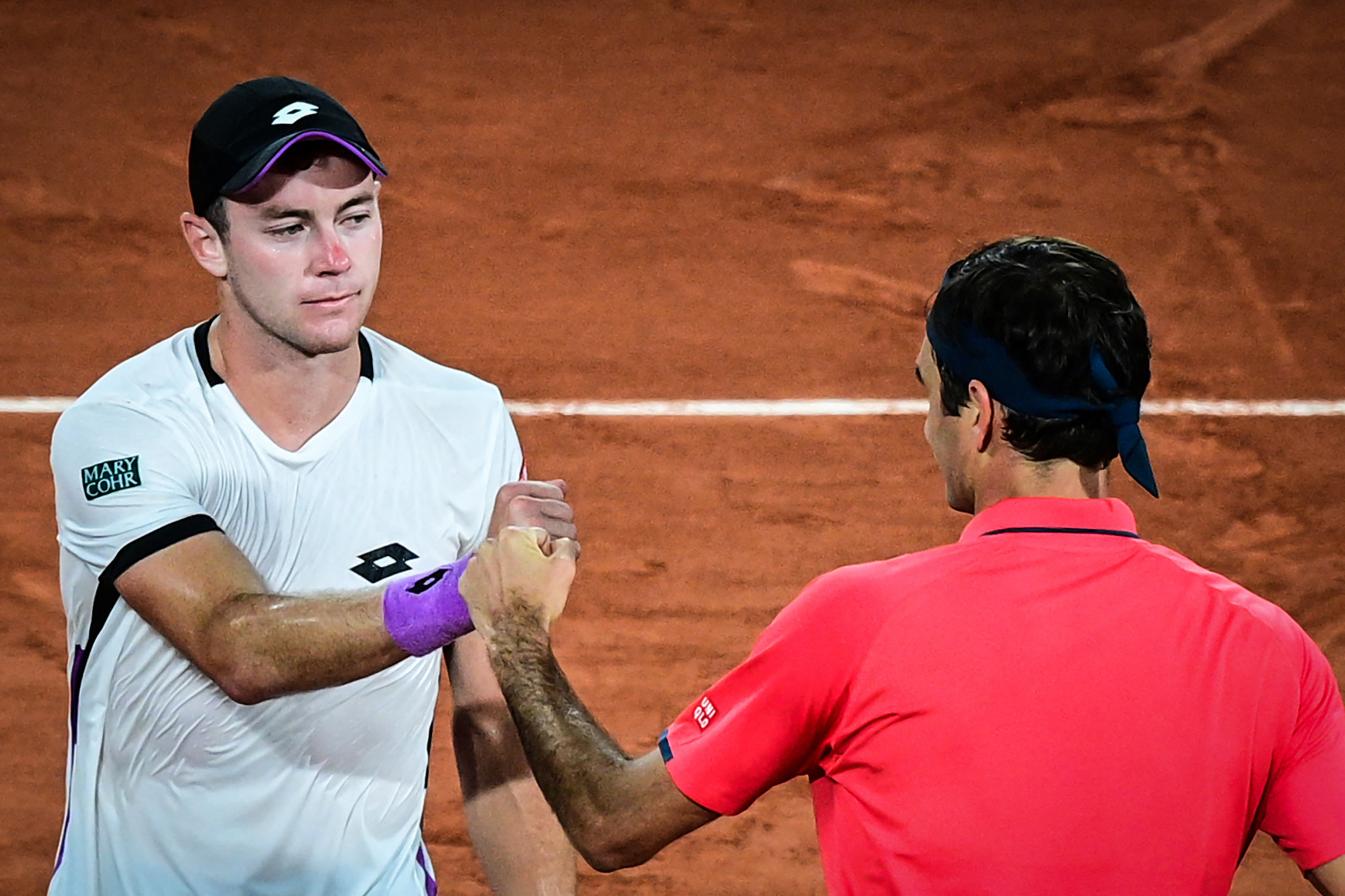 Roger Federer and Dominik Koepfer bump fists after the net after their marathon late-night encounter, which saw the Swiss player prevail in four sets at 12.45am local time  ©Getty Images