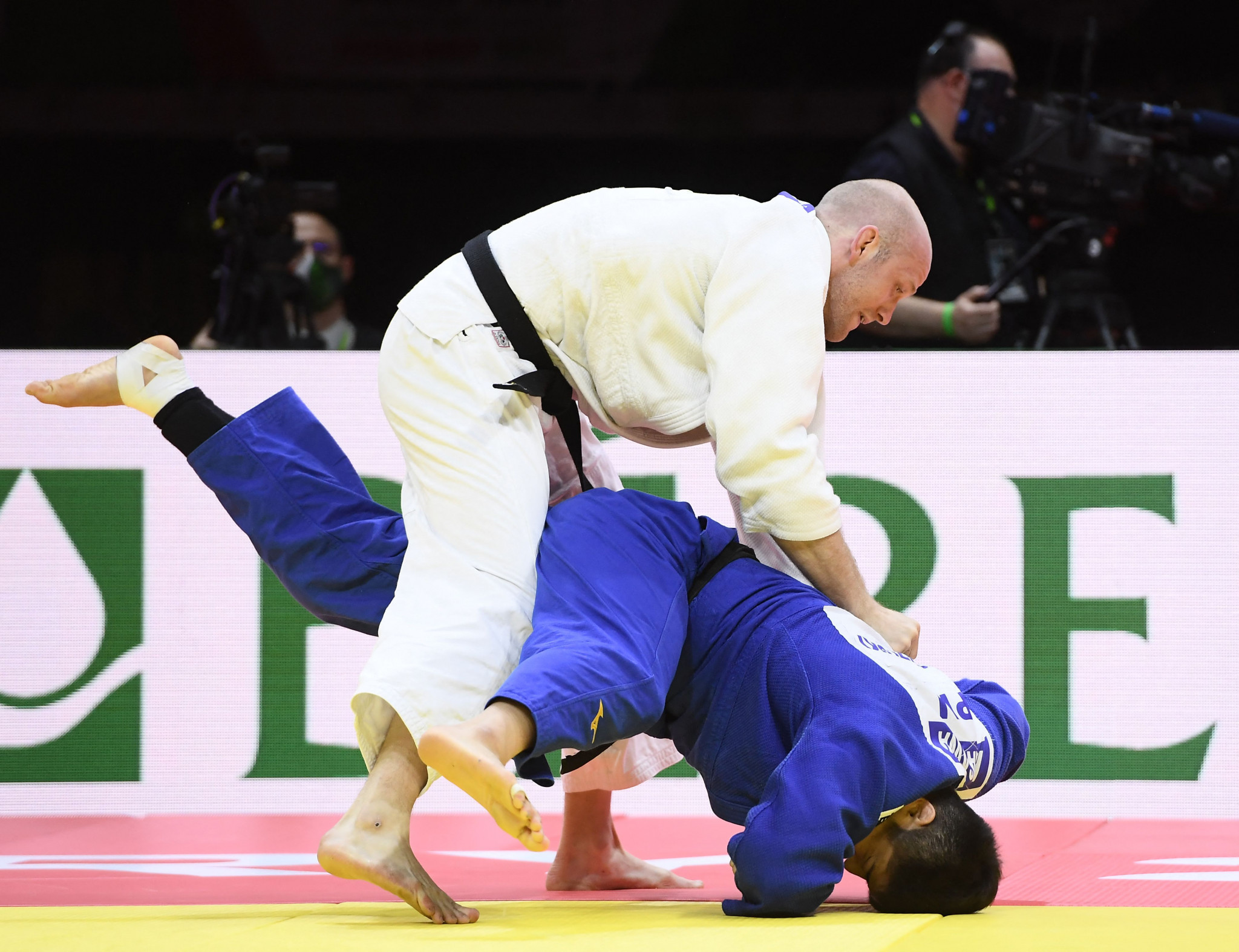 Swede Marcus Nyman, in white, drives Kenta Nagasawa of Japan to the ground during their bronze-medal bout ©Getty Images