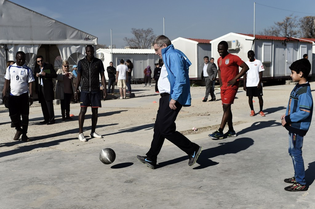 Thomas Bach playing football with youngsters at the Elaionas refugee camp ©Getty Images