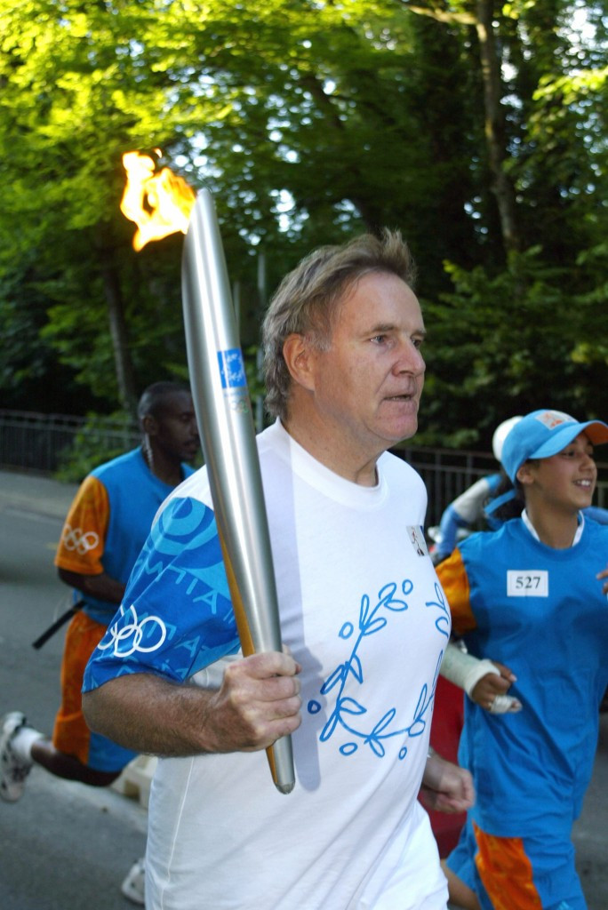 Denis Oswald pictured carrying the Olympic Torch through Lausanne ahead of Athens 2004 ©Getty Images