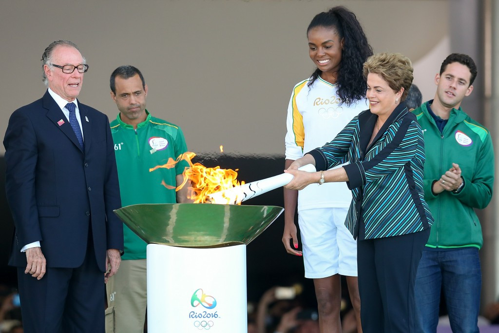 Brazilian President Dilma Rousseff rekindles the Olympic Flame on its arrival in Brazil ©Getty Images