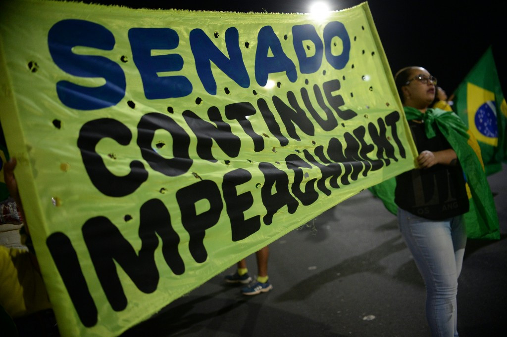 A banner calls on the Senate to continue with impeachment proceedings