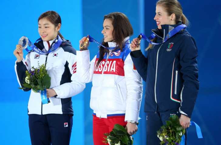 South Korea's 2010 Olympic figure skating champion Yuna Kim (left) manages a smile after her surprising defeat by home skater Adelina Sotnikova at the 2014 Sochi Games ©Getty Images