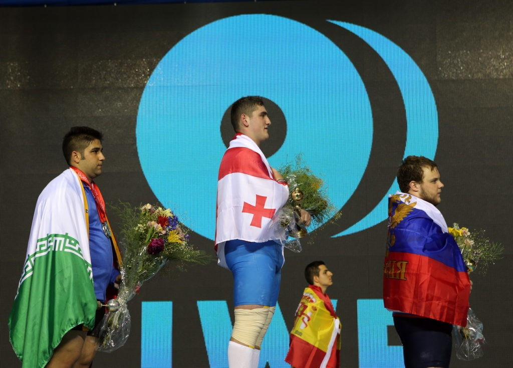 Georgia's Giorgi Chkheidze (centre) delighted the home crowd on the penultimate day of action at the IWF Junior World Championships in Tbilisi, winning the men's 105kg overall title ©IWF