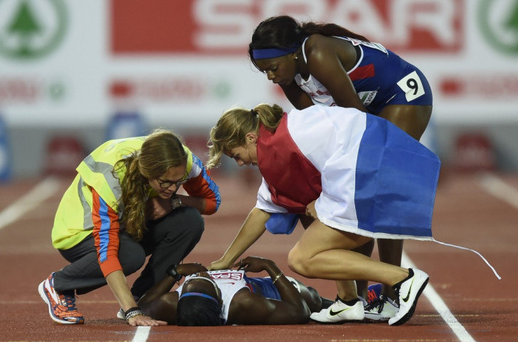 Touch of a champion - Dafne Schippers, winner of the European 100m title, checks on injured training partner Desiree Henry, along with Britain's Asha Philip, before starting her lap of honour ©Getty Images