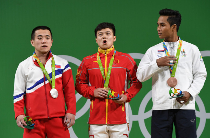 World record holder Long Qingquan celebrates 56kg weightlifting gold alongside London 2012 champion Om Yun Chol of North Korea, left, and bronze medallist Sinphet Kruaithhong of Thailand ©Getty Images