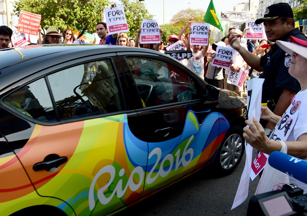 Protesters surround an official Rio 2016 car ©Getty Images