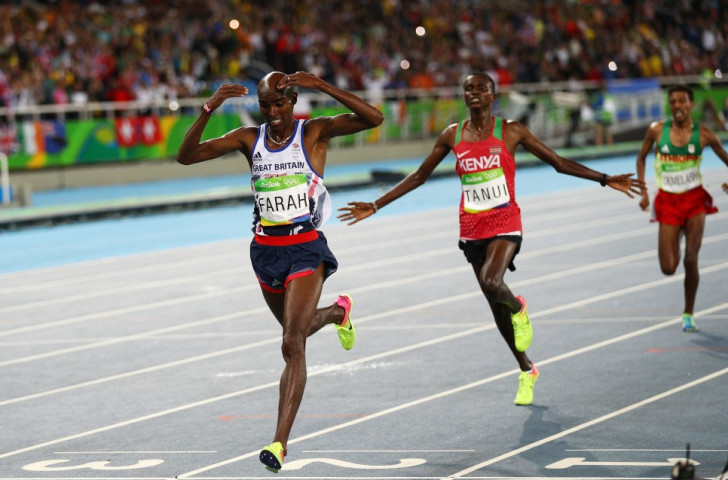 Mo Farah prepares to do the Mobot as he crosses the line having successfully defended his 10,000m title, followed home by Kenya's Paul Tanui and Tamirat Tola of Ethiopia ©Getty Images