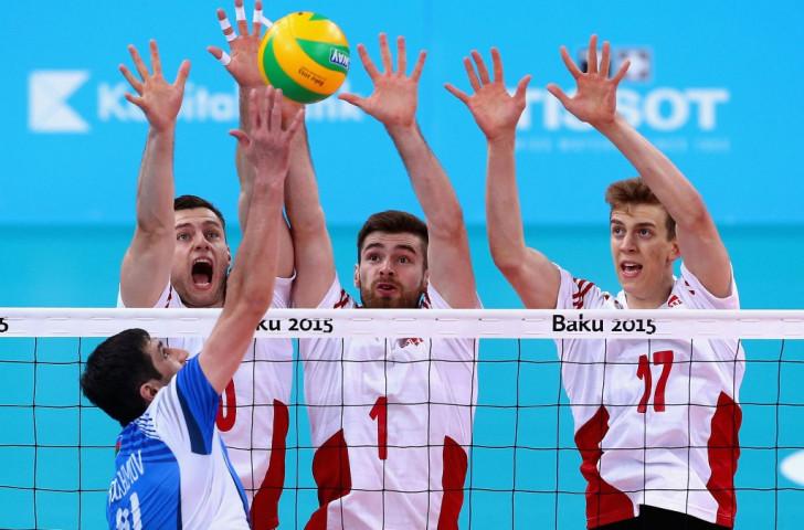 Azerbaijan's Rasul Ibragimov spikes the ball as Poland trio Szymon Romac, Dawid Dryja and Artur Szalpuk attempt to block in the men's  volleyball preliminary Pool A match ©Getty Images