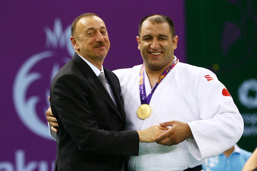 Azerbaijan's President  Ilham Aliyev briefly joined judoka Ilham Zakiyev on top of the podium after presenting him his gold medal