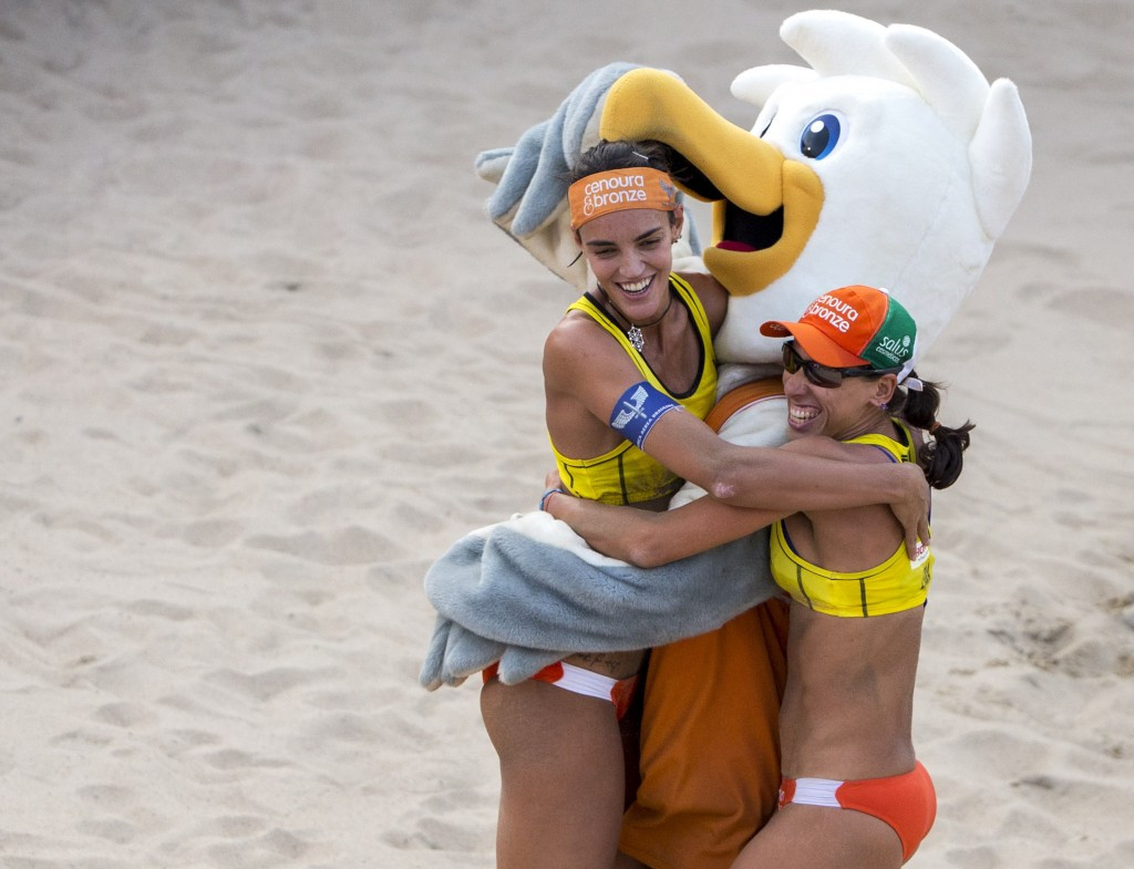 Brazil's Fernanda Alves and Tatiana Lima hug the mascot Spike after winning their semi-final match ©Getty Images