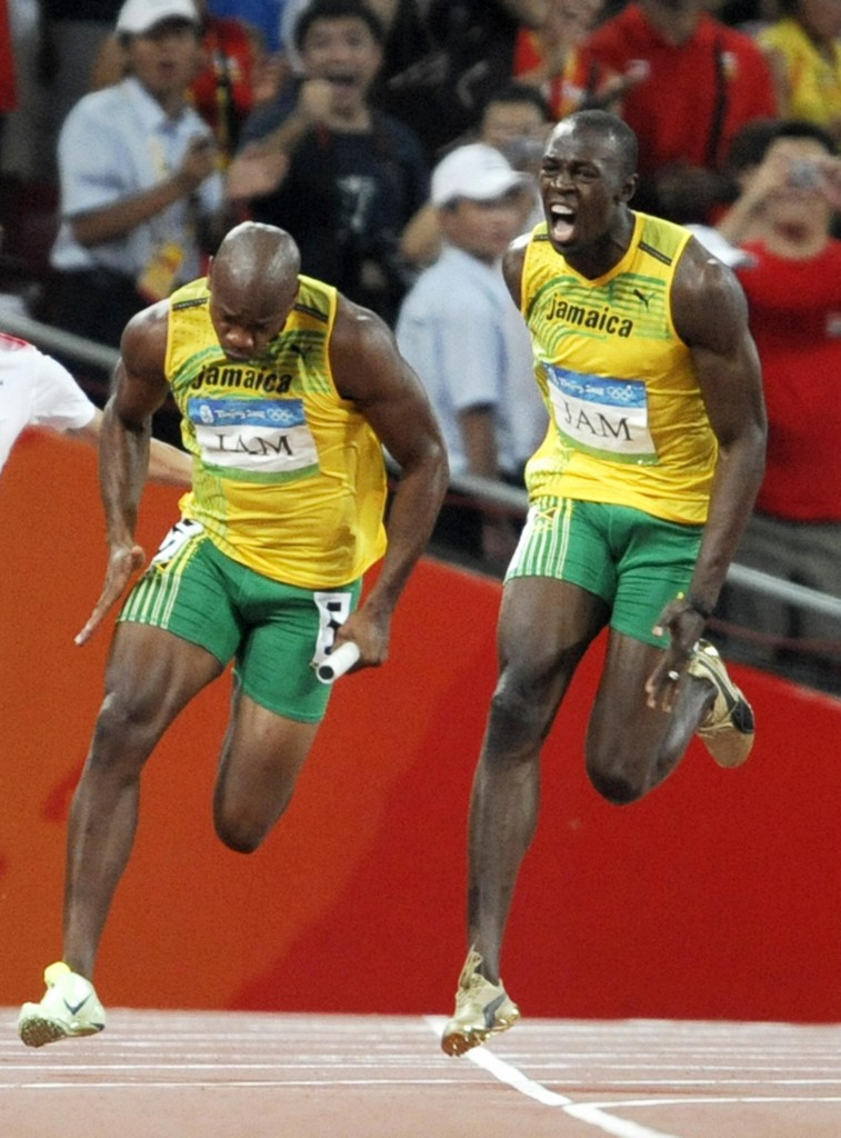 Usain Bolt urges his colleague Asafa Powell towards the line during Jamaica's 4x100m victory at the Beijing 2008 Olympics in a world record of 37.10 ©Getty Images