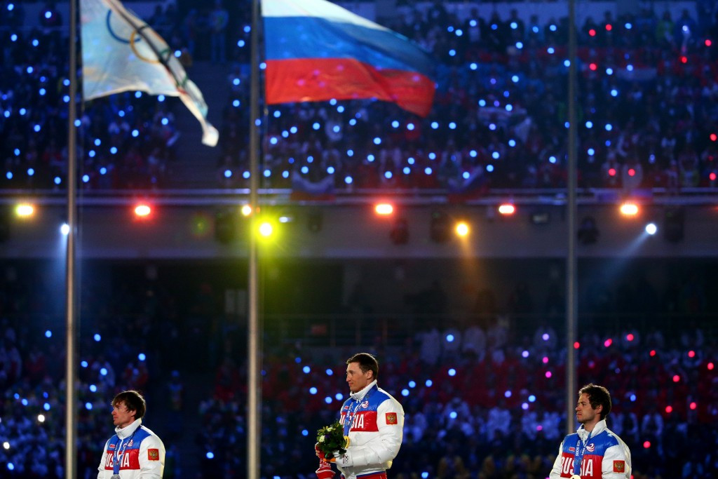 Aleksandr Legkov, centre, pictured receiving his 50km mass start cross country gold medal at the Closing Ceremony of Sochi 2014, is among those currently suspended ©Getty Images