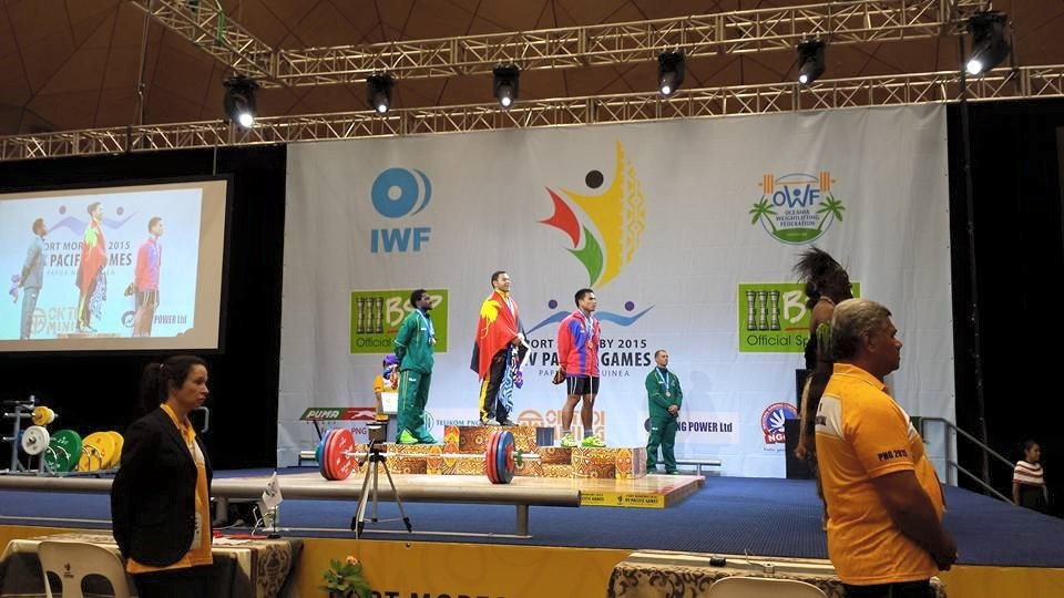 Weightlifter Philip Toua Udia stands atop the Pacific Games podium having received the men's 77kg overall gold medal ©ITG