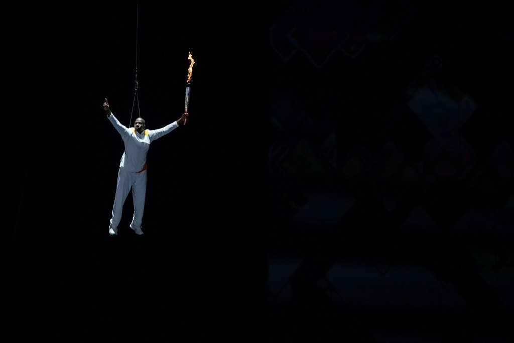 Donovan Bailey is lowered into the stadium with the Pan American Games Torch ©Getty Images