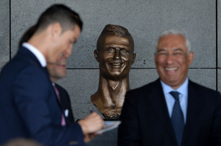 Cristiano Ronaldo, pictured at the ceremony re-naming Madeira Airport after him, appears to be taking in good heart the appearance of a bronze bust depicting Niall Quinn ©Getty Images